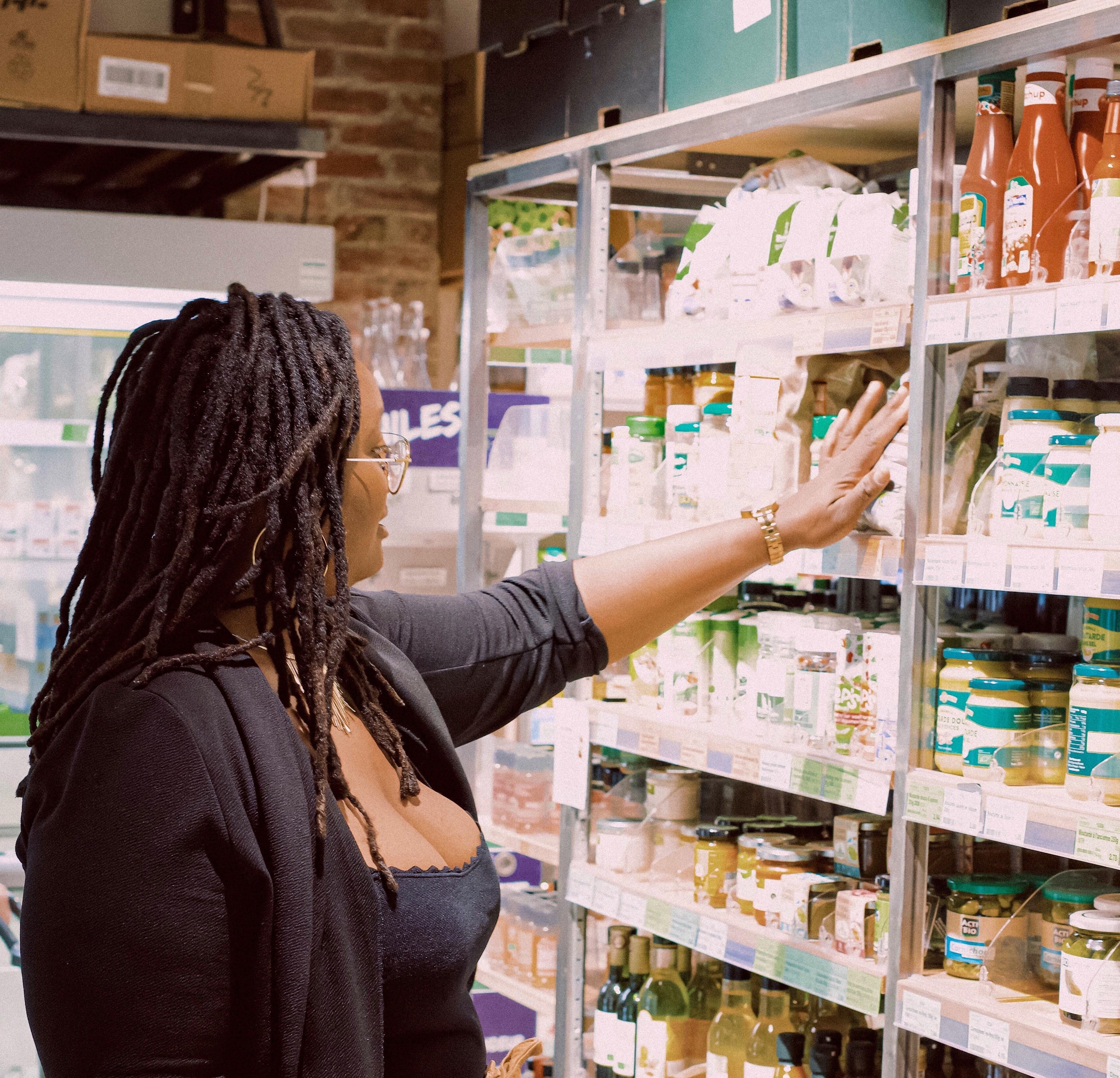 Femme pesant son choix dans un rayon d'un magasin.