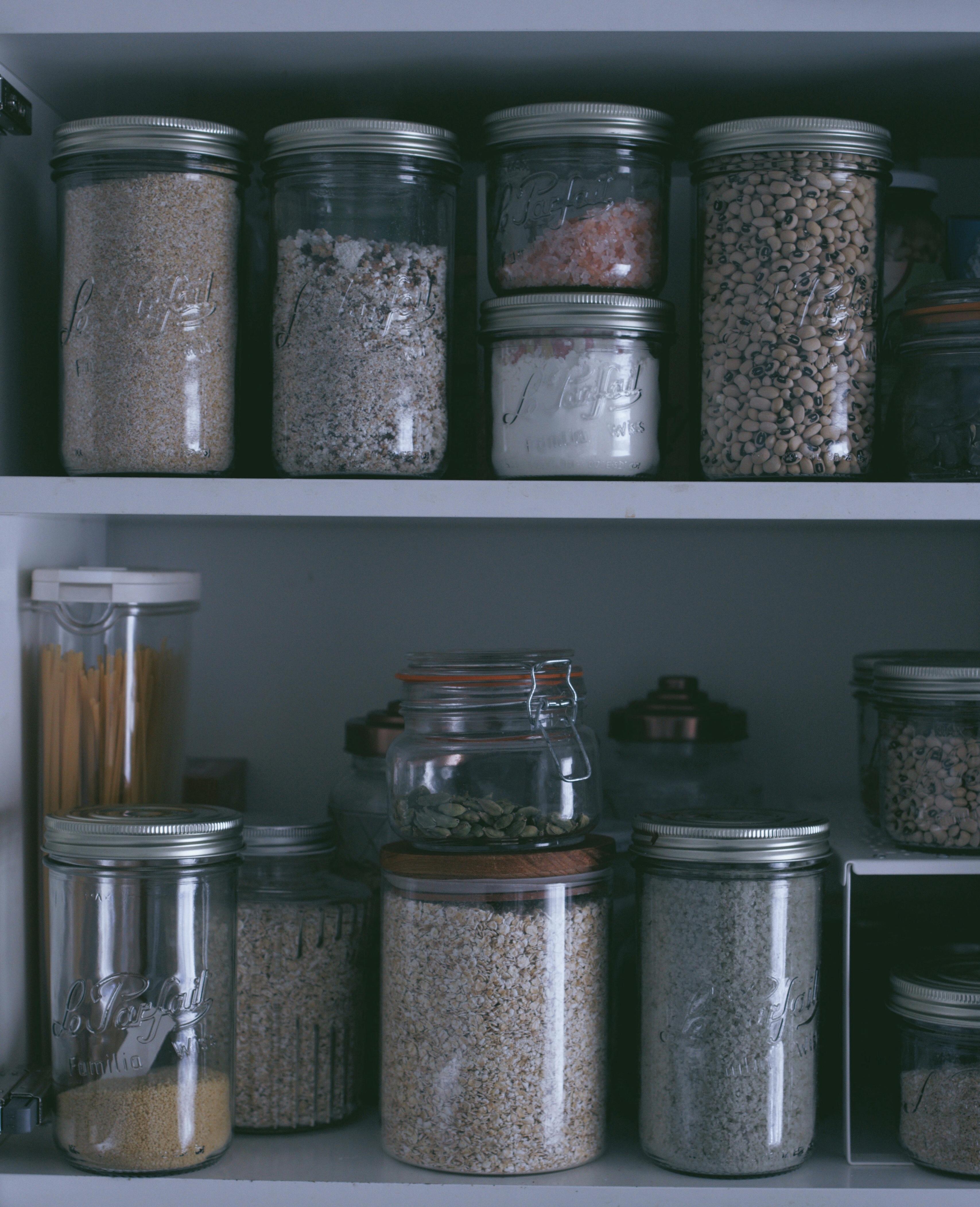 placard de cuisine rangé avec des bocaux en verre rempli de graine oléagineuses.