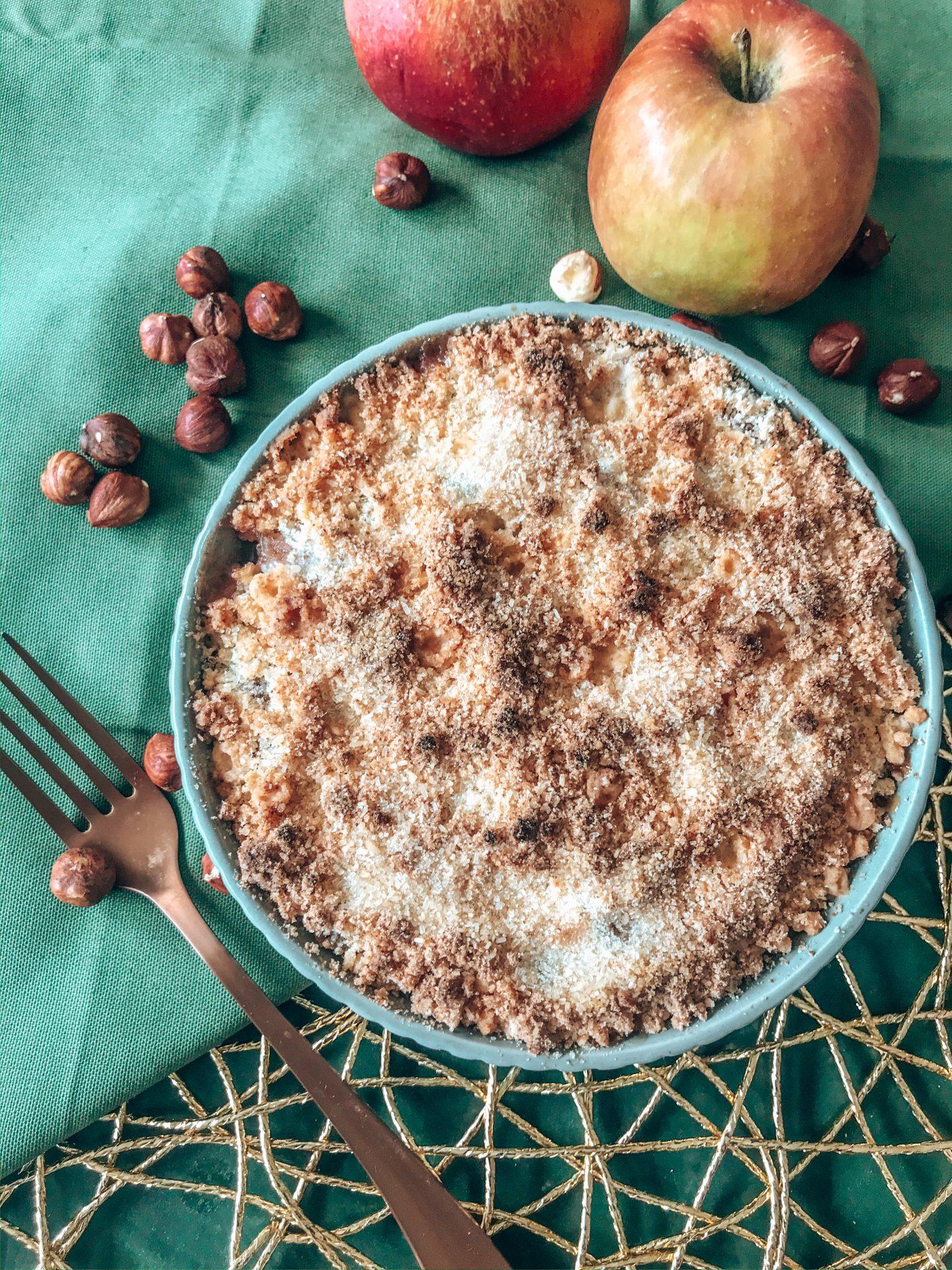 crumble aux pommes et coco avec deux pommes rouges, des noisettes et une fourchette.